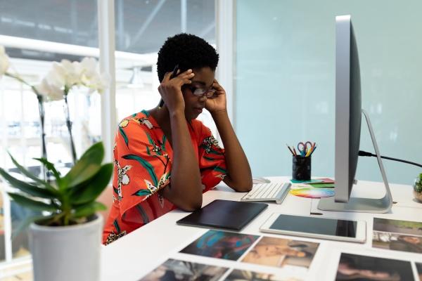 gestresste grafikdesignerin sitzt am schreibtisch