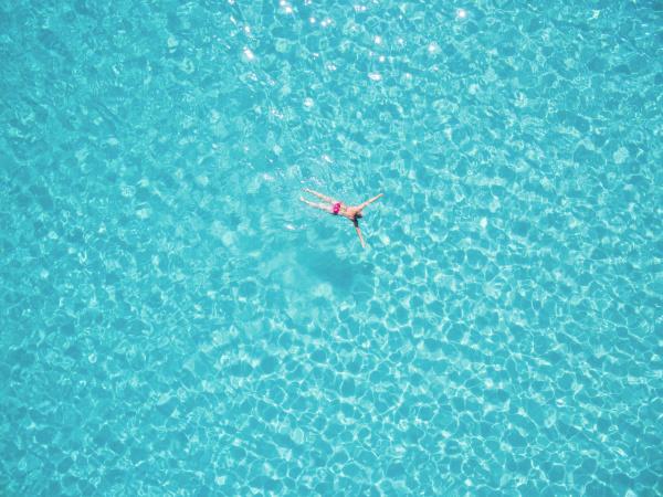 schoene frau schwimmen in transparentem meer