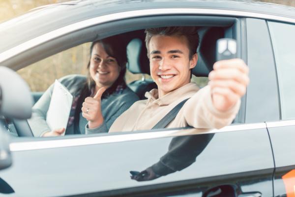 gluecklicher schueler der fahrschule zeigt autoschluessel