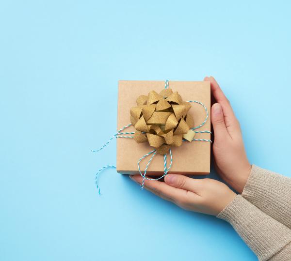 weibliche hand haelt eine quadratische box