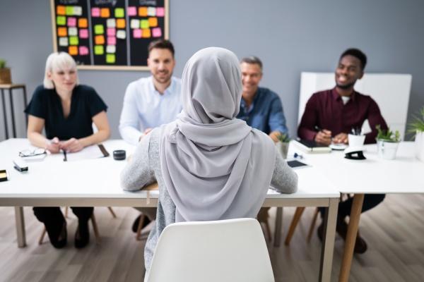 muslimische frau in hijab sitzen bei