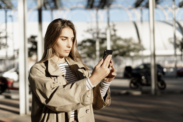 junge blonde frau mit smartphone und
