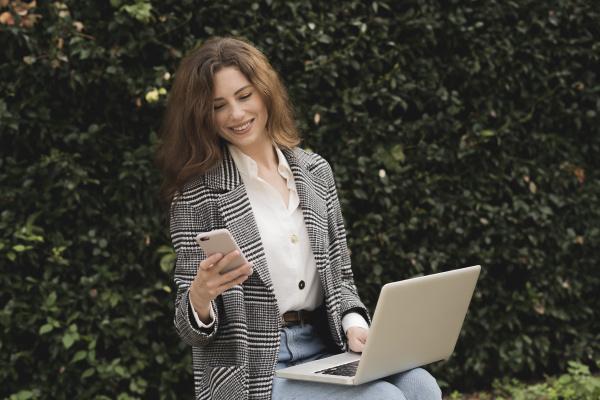 laechelnde frau mit smartphone und laptop