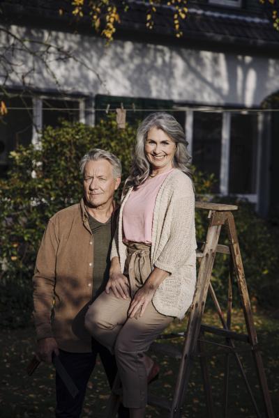 seniorenpaar mit leiter im garten ihres