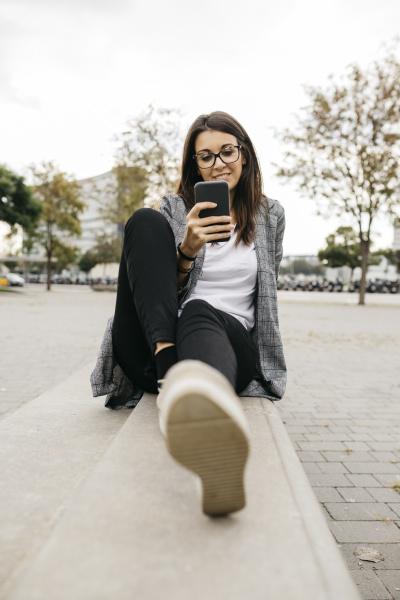 junge geschaeftsfrau mit smartphone sitzt auf