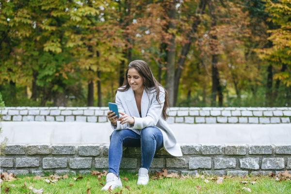 laechelnde frau mit ihrem smartphone in