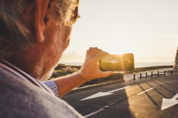 AElterer mann mit smartphone und foto
