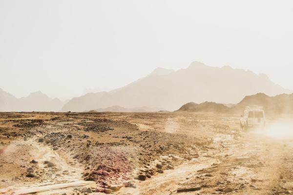gelaendewagen bewegt sich auf trockener landschaft