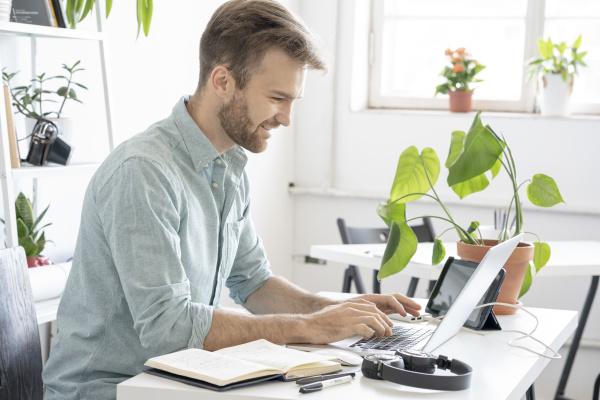 laechelnder mann mit laptop am schreibtisch