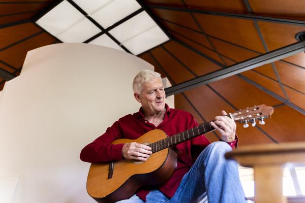 AElterer mann der zu hause gitarre