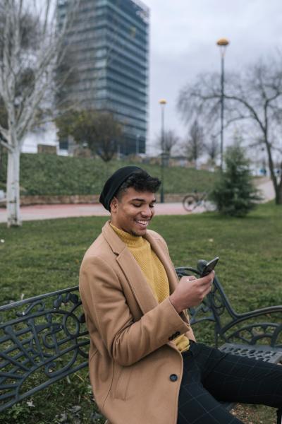 laechelnder junger mann sitzt mit handy