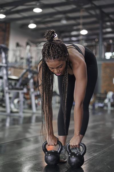 sportlerinnen trainieren mit kettlebells im fitnessstudio