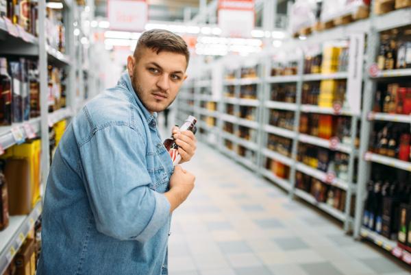 mann versteckt flasche alkohol unter seinem