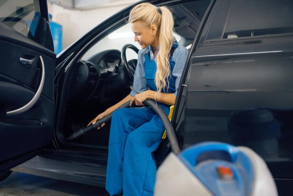 weibliche waschmaschine mit staubsauger reinigt auto
