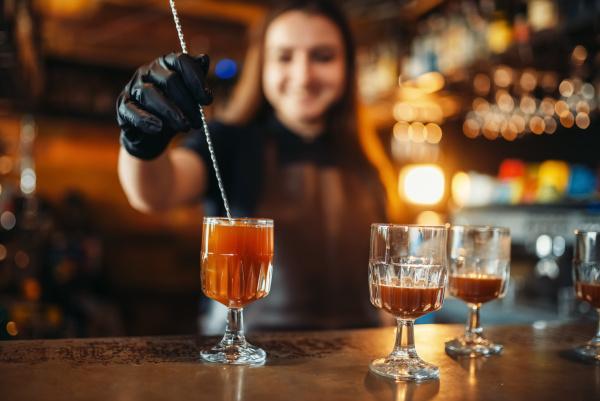barkeeperin macht coctail an der theke