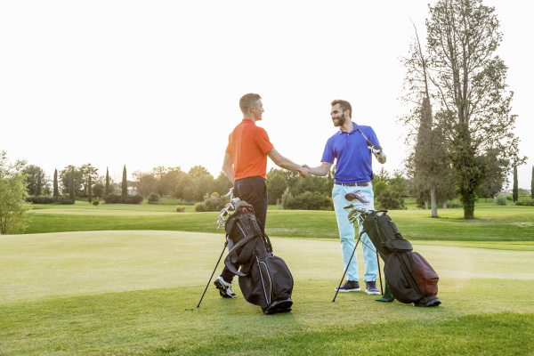 freunde schuetteln haende auf golfplatz