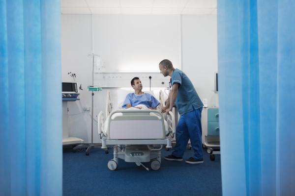 maennliche krankenschwester im gespraech mit patient