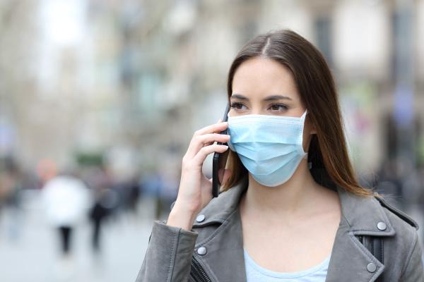 frau mit maske am telefon auf