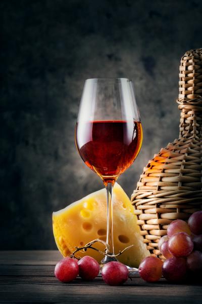 glas rotwein mit trauben und korbflasche