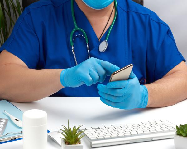 arzt in blauer AErzteuniform sitzt an