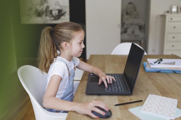 maedchen sitzt vor ihrem laptop waehrend