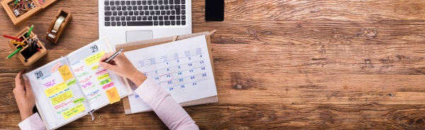 geschaeftsfrau schreibt zeitplan in kalendertagebuch