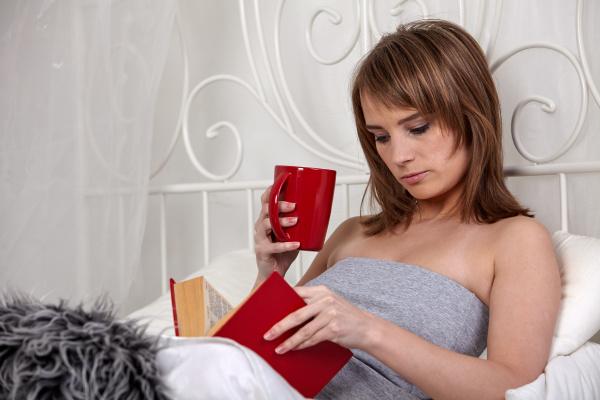 junge frau liest buch im schlafzimmer