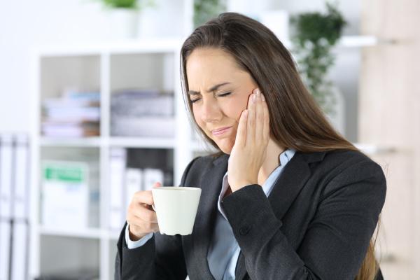 exekutive mit zahnschmerzen haelt kaffee im