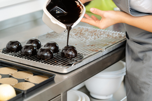 konditor giesst fluessige schokolade ueber ein