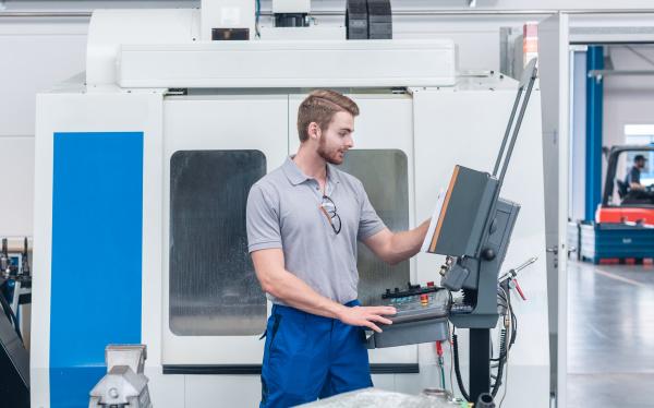arbeiter mit computergesteuerter werkzeugmaschine