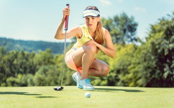 frau auf golfplatz nimmt mass auf