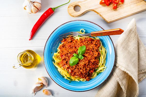 koestliche spaghetti bolognese auf weissem hintergrund
