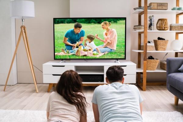 glueckliche familie schaut fernsehen oder film