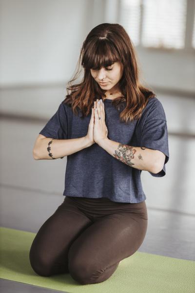 ballerina meditiert in gebetsposition auf UEbungsmatte