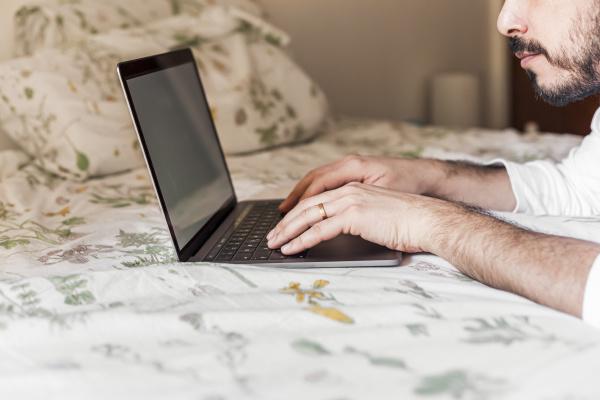 mann mit laptop auf dem bett
