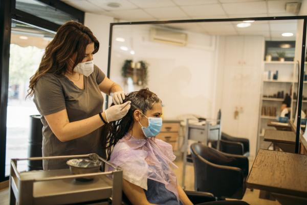 weibliche friseurin mit maske faerbung haar