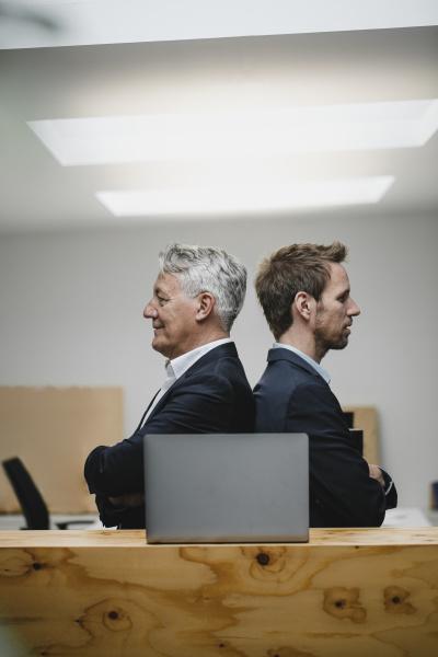 zwei selbstbewusste geschaeftsleute sitzen im buero