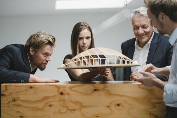 erfolgreiche geschaeftsleute die sich mit architekturmodell