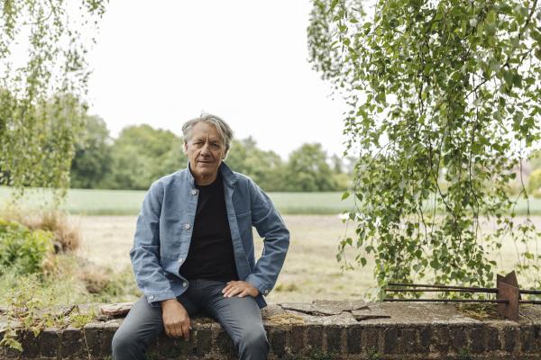 senior mann sitzt auf einer ziegelmauer