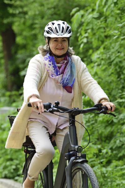 glueckliche seniorin faehrt elektrofahrrad auf fussweg