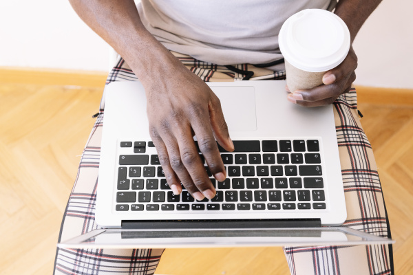 junger geschaeftsmann mit laptop beim sitzen