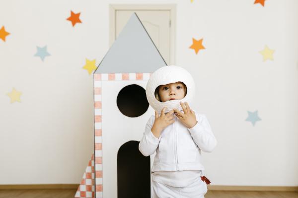 maedchen im kostuem und spielt astronaut
