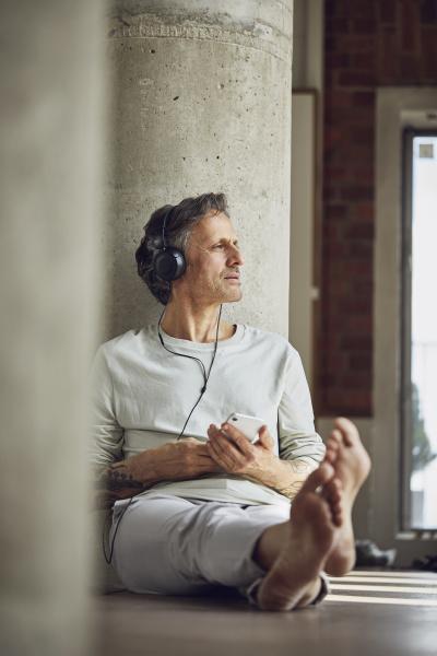senior mann mit kopfhoerern hoeren musik