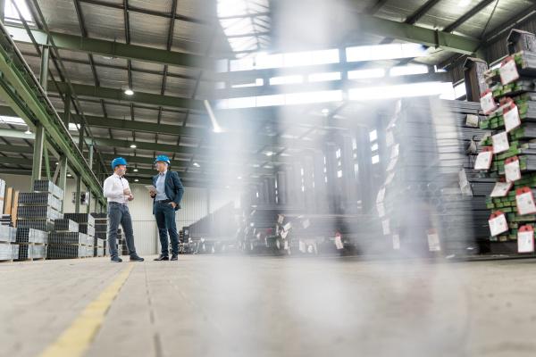 zwei geschaeftsleute sprechen in einer fabrik