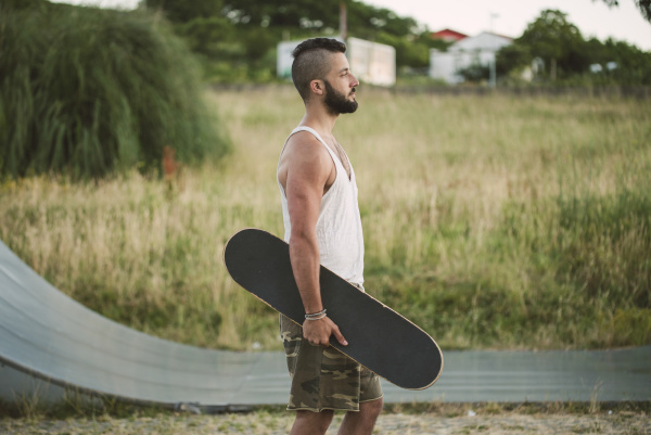 handsome, young, man, holding, skateboard, looking - 28759531