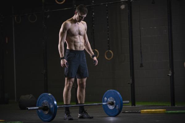 mann der im fitnessstudio kniebeugen trainiert