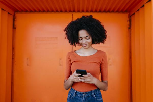 laechelnde junge frau mit smartphone waehrend