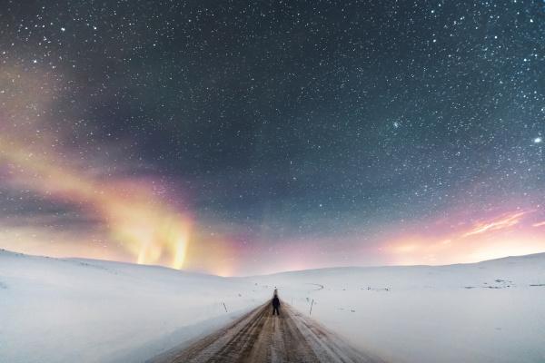 mann steht auf landstrasse unter sternenhimmel