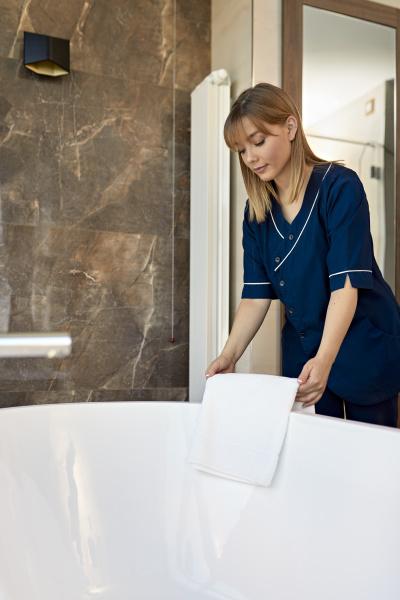 zimmermaedchen legt handtuch auf badewanne waehrend