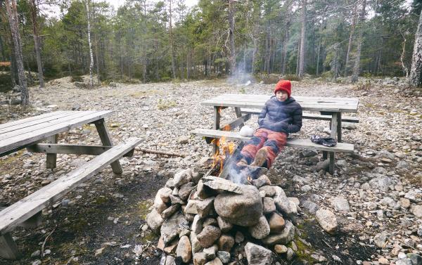 junge sitzt auf picknickbank neben lagerfeuer